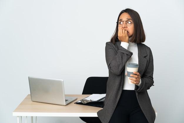 Jeune femme d'affaires latine travaillant dans un bureau isolé sur blanc nerveux et effrayé mettant les mains à la bouche