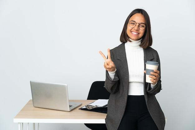 Jeune femme d'affaires latine travaillant dans un bureau isolé sur blanc souriant et montrant le signe de la victoire
