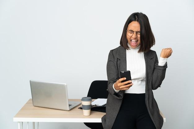 Jeune femme d'affaires latine travaillant dans un bureau isolé sur blanc avec téléphone en position de victoire