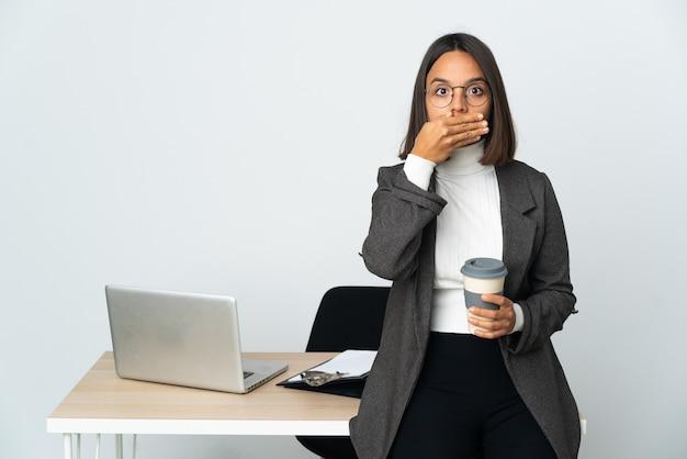 Jeune femme d'affaires latine travaillant dans un bureau isolé sur fond blanc couvrant la bouche avec les mains