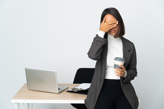 Jeune femme d'affaires latine travaillant dans un bureau isolé sur fond blanc couvrant les yeux par les mains
