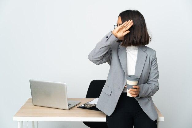 Jeune femme d'affaires latine travaillant dans un bureau isolé sur fond blanc étirement nerveux des mains vers l'avant