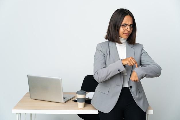 Jeune femme d'affaires latine travaillant dans un bureau isolé sur fond blanc faisant le geste d'être en retard