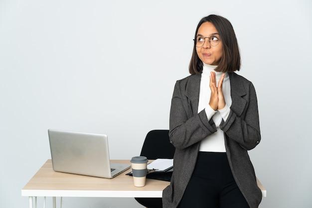 Jeune femme d'affaires latine travaillant dans un bureau isolé sur fond blanc intrigant quelque chose