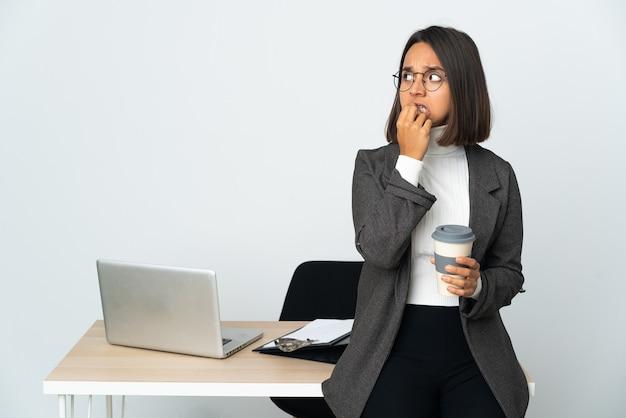 Jeune femme d'affaires latine travaillant dans un bureau isolé sur fond blanc nerveux et effrayé
