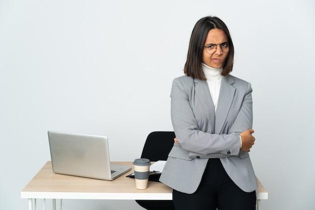 Jeune femme d'affaires latine travaillant dans un bureau isolé sur fond blanc se sentir contrarié