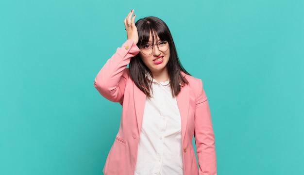 Jeune femme d'affaires levant la paume vers le front pensant oops, après avoir fait une erreur stupide ou s'être souvenue, se sentir stupide