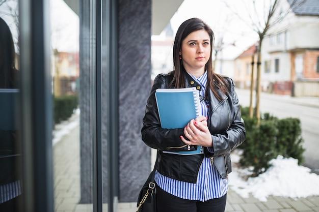 Jeune femme d'affaires avec des livres sur le trottoir