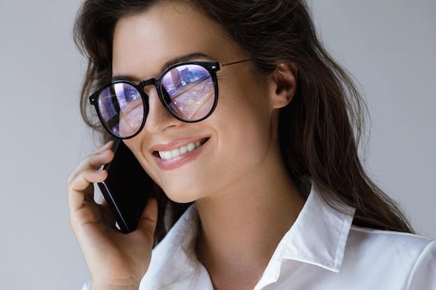 Jeune, femme affaires, lunettes, conversation, smartphone