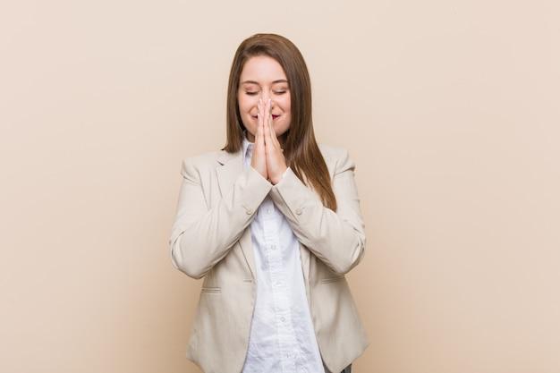 Jeune femme d'affaires, main dans la main, priez près de la bouche, se sent confiant.