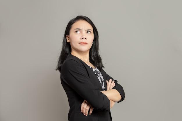 Jeune femme d'affaires en manteau noir croisant les bras tout en levant les yeux