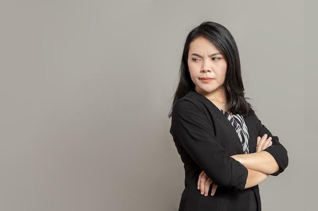 Jeune femme d'affaires en manteau noir croisant les bras tout en regardant en arrière