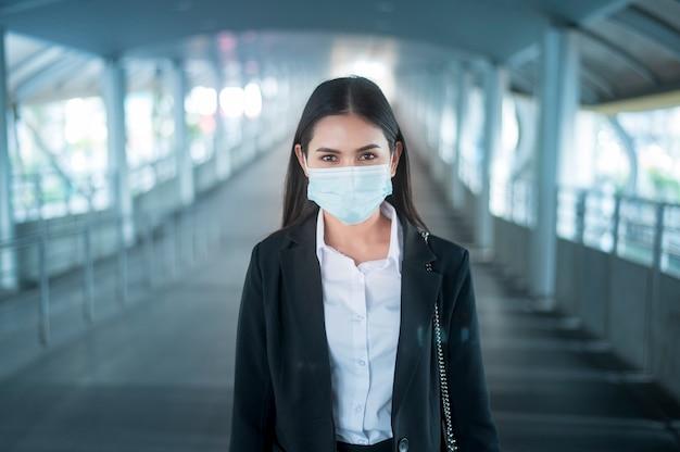 Jeune femme d'affaires avec masque facial est debout sur la plate-forme de métro à l'aide de smart