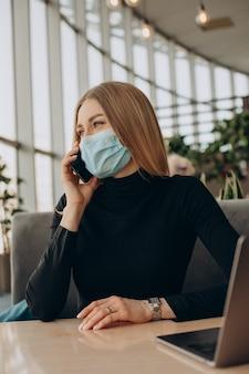 Jeune femme d'affaires en masque travaillant sur ordinateur portable dans un café