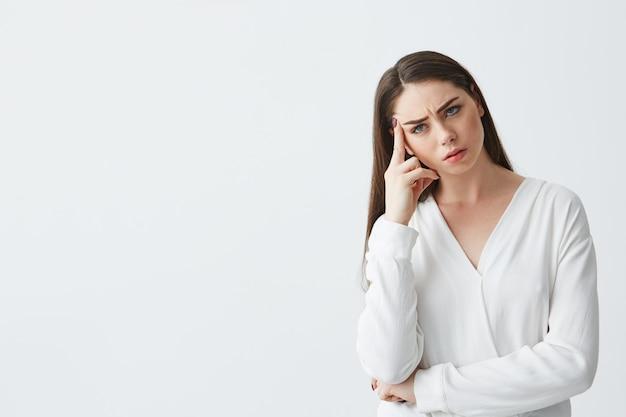 Jeune femme d'affaires mécontent pensant avec le doigt près du temple.