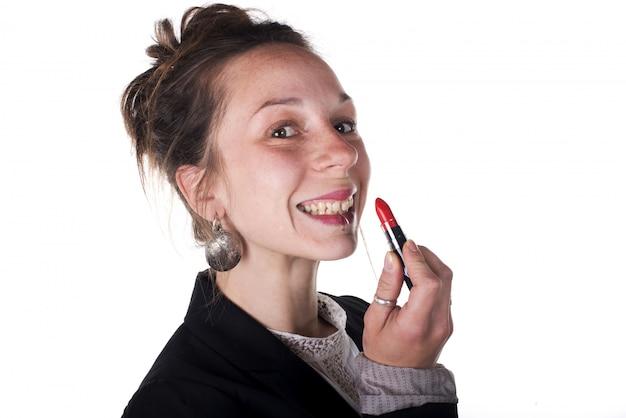 Jeune femme d'affaires met du rouge à lèvres
