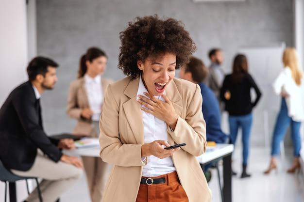 Jeune femme d'affaires métisse excitée debout au bureau et lecture de message au téléphone.