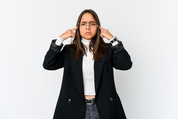 Jeune femme d'affaires métisse isolée sur un espace blanc concentré sur une tâche, gardant l'index pointant la tête.