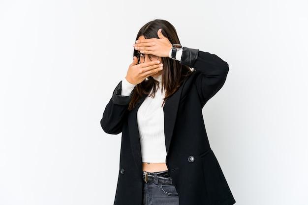 Jeune femme d'affaires métisse isolée sur fond blanc clignote à la caméra à travers les doigts, visage couvrant embarrassé.