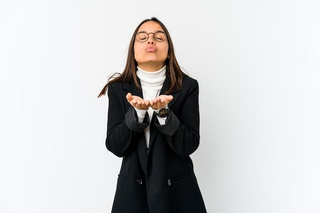 Jeune femme d'affaires métisse isolée sur fond blanc, plier les lèvres et tenant les paumes pour envoyer l'air baiser.