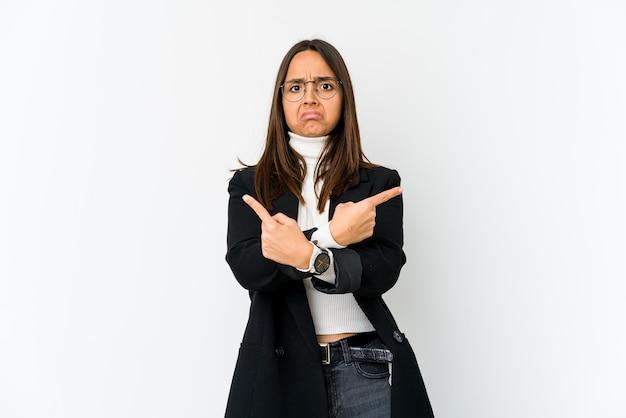 Jeune femme d'affaires métisse isolée sur fond blanc pointe sur le côté, essaie de choisir entre deux options.