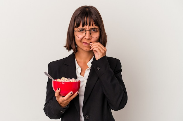 Jeune femme d'affaires métisse mangeant des céréales isolées sur fond blanc avec les doigts sur les lèvres gardant un secret.