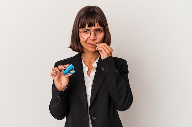 Jeune femme d'affaires métisse tenant une agrafeuse isolée sur fond blanc avec les doigts sur les lèvres gardant un secret.