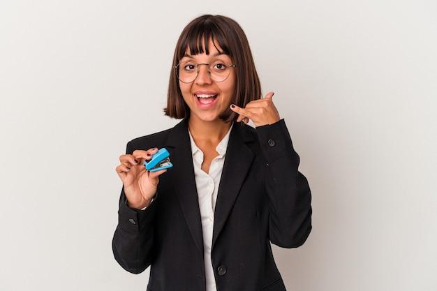Jeune femme d'affaires métisse tenant une agrafeuse isolée sur fond blanc montrant un geste d'appel de téléphone portable avec les doigts.