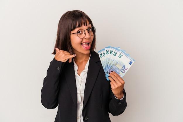 Jeune femme d'affaires métisse tenant un billet isolé sur fond blanc montrant un geste d'appel de téléphone portable avec les doigts.