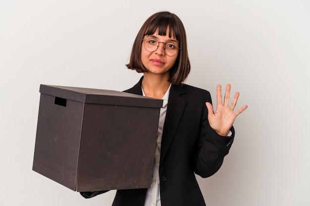 Jeune femme d'affaires métisse tenant une boîte isolée sur fond blanc souriant joyeux montrant le numéro cinq avec les doigts.