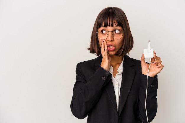 Jeune femme d'affaires métisse tenant un chargeur de téléphone isolé sur fond blanc souriant et levant le pouce vers le haut