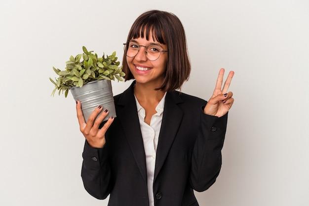 Jeune femme d'affaires métisse tenant une plante isolée sur fond blanc montrant le numéro deux avec les doigts.