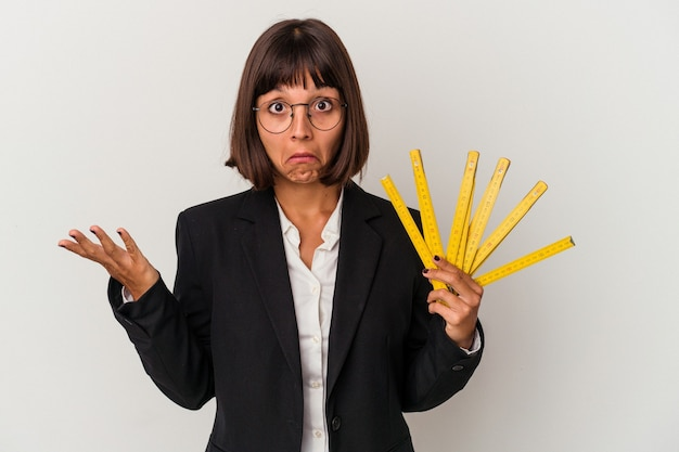 Jeune femme d'affaires métisse tenant un ruban à mesurer isolé sur fond blanc hausse les épaules et ouvre les yeux confus.