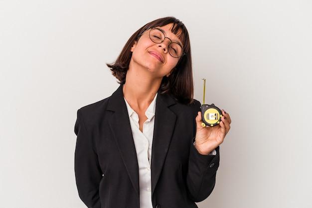 Jeune femme d'affaires métisse tenant un ruban à mesurer isolé sur fond blanc rêvant d'atteindre des objectifs et des buts