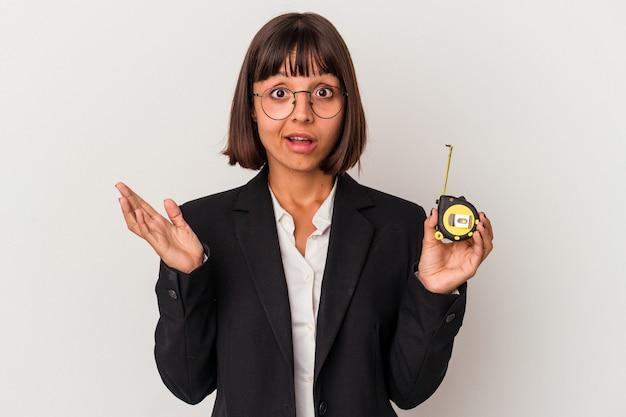 Jeune femme d'affaires métisse tenant un ruban à mesurer isolé sur fond blanc surpris et choqué.