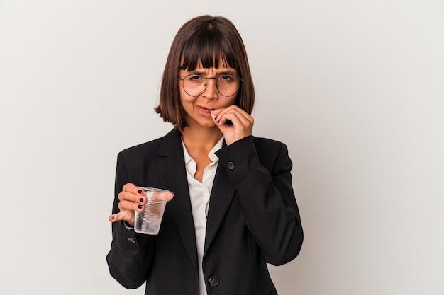 Jeune femme d'affaires métisse tenant un verre d'eau isolé sur fond blanc avec les doigts sur les lèvres gardant un secret.