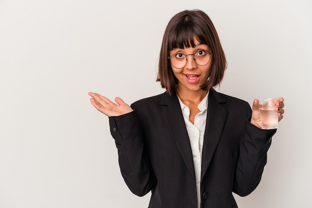 Jeune femme d'affaires métisse tenant un verre d'eau isolé sur fond blanc montrant un espace de copie sur une paume et tenant une autre main sur la taille.