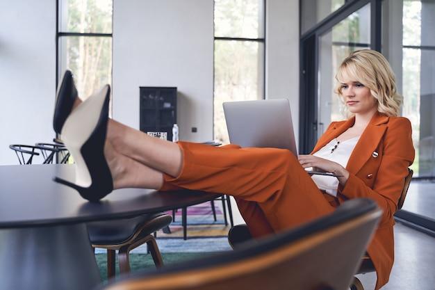 Jeune femme d'affaires à la mode concentrée avec ses jambes sur la table travaillant dans son bureau