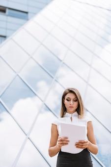Jeune femme d'affaires moderne lisant des documents