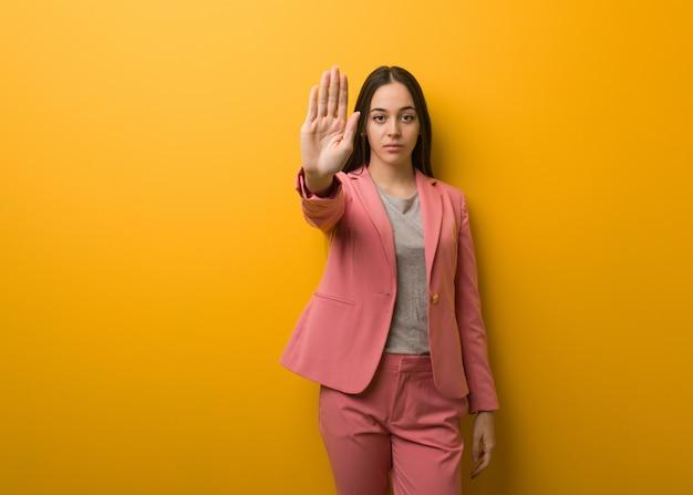 Jeune femme d'affaires moderne mettant la main devant
