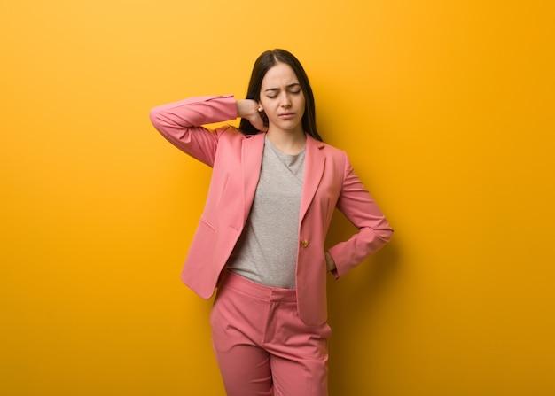 Jeune femme d'affaires moderne souffrant de douleurs au cou