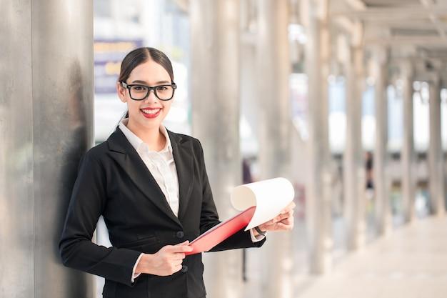 Jeune femme d'affaires moderne souriante à la recherche de paper board avec espace de copie