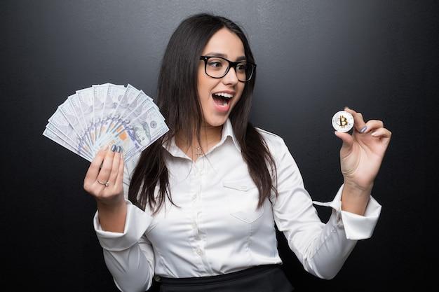 Jeune femme d'affaires moderne avec succès tenant un bitcoin d'or et un dollar en espèces isolé sur un mur noir