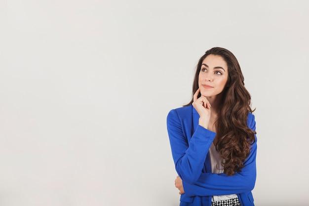 Jeune femme d'affaires montrant avec un geste réfléchi