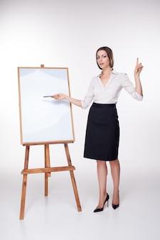 Jeune femme d'affaires montrant quelque chose sur le mur blanc