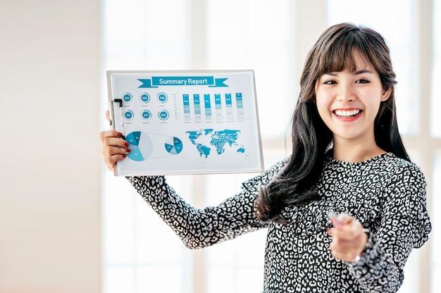 Jeune femme d'affaires montrant le rapport avec le diagramme dans le bureau moderne.
