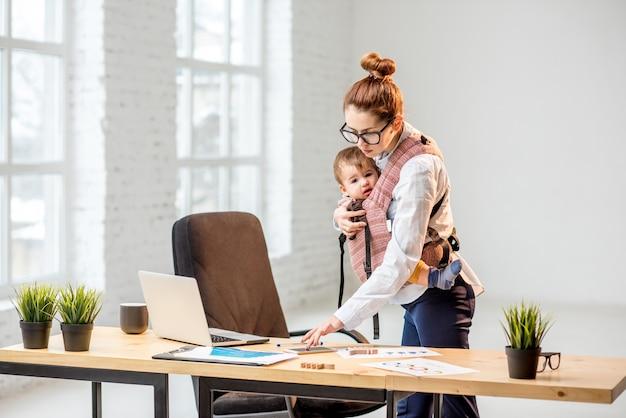 Jeune femme d'affaires multitâche debout avec son bébé pendant le travail au bureau
