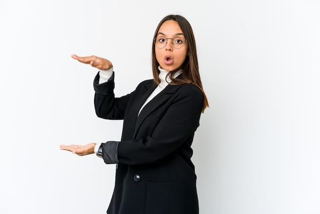 Jeune femme d'affaires sur un mur blanc choqué et étonné tenant un espace vide entre les mains.