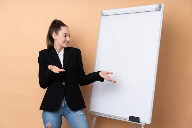 Jeune femme d'affaires sur un mur isolé donnant une présentation sur tableau blanc et avec une expression surprise