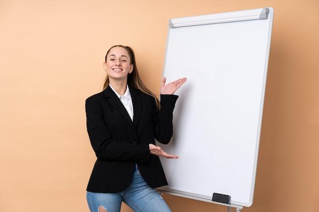 Jeune femme d'affaires sur un mur isolé donnant une présentation sur tableau blanc